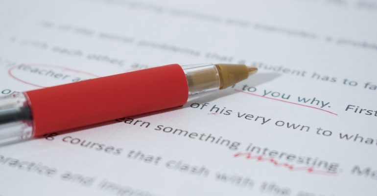 A red pen and a paper with underlined words